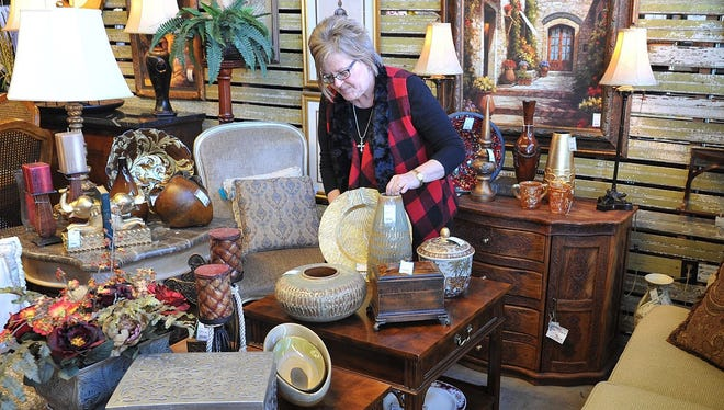 Jan Saville, owner of Hello Again, sets up a display of antique furniture and other home decor pieces. Saville will be one of 18 interior designers sprucing up a house for the Decorator Show House, coming up April 28-30 at 2011 Hampstead.