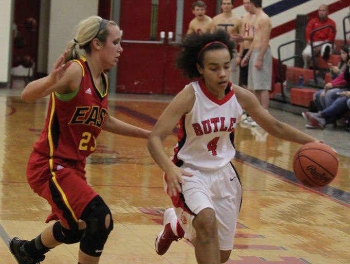 Butler High School's Tasia Jefferies (4) battles pressure from Bullitt East High School's Taylor Blain (23) during the first half of play at Butler High School in Louisville, Kentucky. .          December 11, 2013.