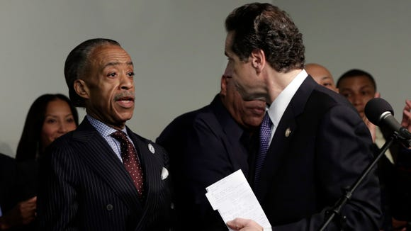 The Rev. Al Sharpton, left, shakes hands with New York Gov. Andrew Cuomo during his appearance at Sharpton's National Action Network headquarters to kick off the Martin Luther King Jr. holiday weekend in New York.