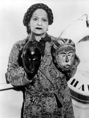 In this 1934 photo, Rubinstein shows two masks from her collection of African, Oceanic and Latin American art.