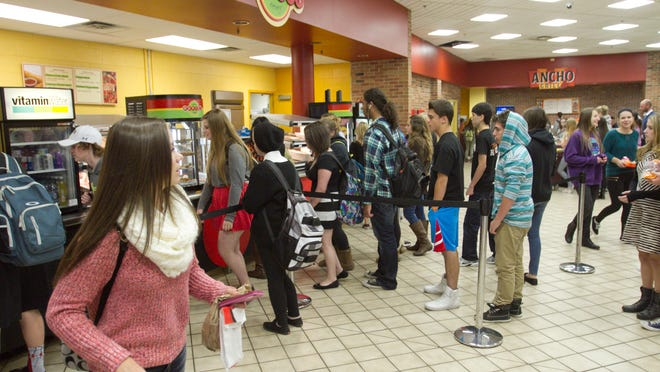 Students line up to make their selections in the dining area of Brighton High School, which offers free or reduced-cost lunches.