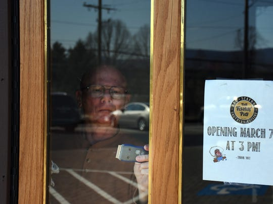 Jack Dunford, father-in-law of co-owner Leighton Justice, helps clean a label from a window as the Fishin' Pig restaurant prepares to open this week.