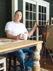 John Grieco sits in his home at a table that he constructed.