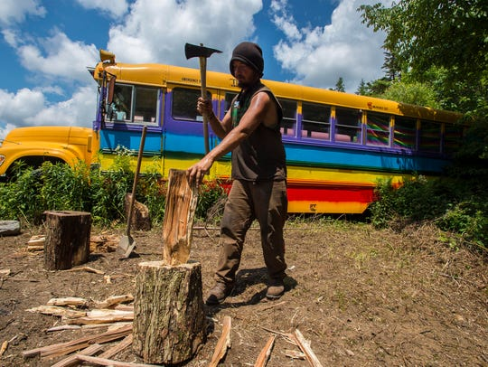 Joe chops wood for a camp fire at the Bus Village at