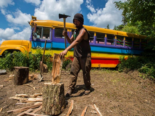 Joe chops wood for a camp fire at the Bus Village at the Rainbow Family National Gathering in the Green Mountain National Forest in Mt. Tabor on Tuesday, June 28, 2016.