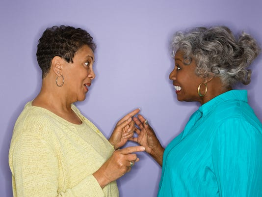 Women pointing at eachother.