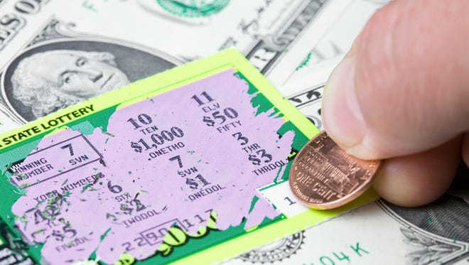 A lottery player has scratched a winning ticket which rests on a dollar bill background. The 7 in the Winning Number box matches the 7 mid-frame, resulting in a $1.00 win.