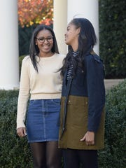 President Barack Obama's daughters Sasha and Malia smile during the annual turkey-pardoning ceremony at the White House on Wednesday, Nov. 25 2015, in Washington, D.C.