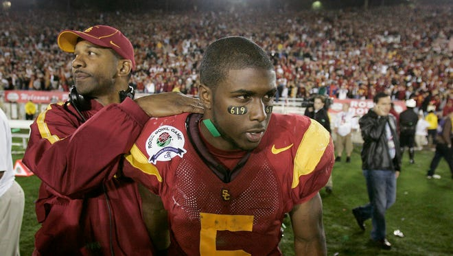 This Jan. 4, 2006, file photo shows Southern California's Reggie Bush, right, being consoled by USC running back coach Todd McNair after their 41-38 loss to Texas in the Rose Bowl.