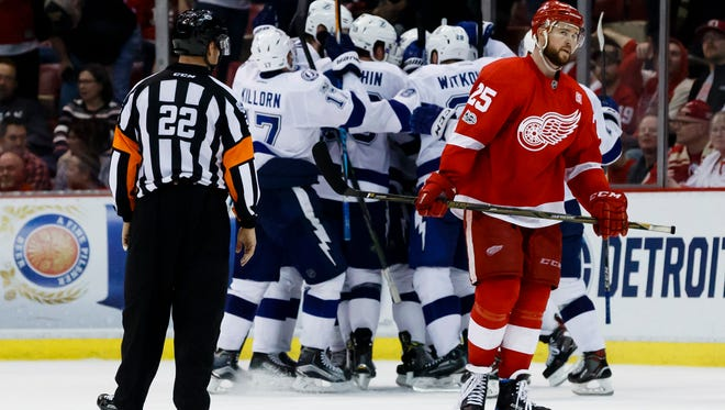 Red Wings defenseman Mike Green (25) skates off the ice as the Lightning celebrate after the Wings' 2-1 overtime loss Friday at Joe Louis Arena.