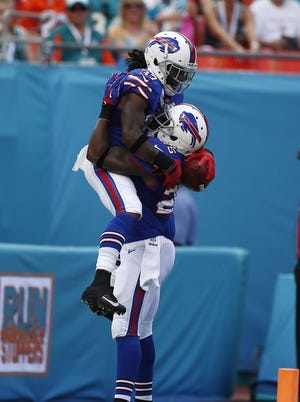 Buffalo Bills defensive back Nickell Robey (left) is lifted in the air by strong safety Da'Norris Searcy (25) after his interception of a touchdown against the Dolphins.