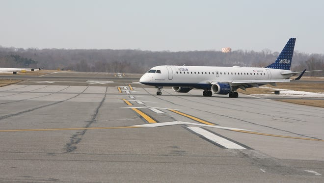 A Jet Blue plane crosses Runway 29 at the Westchester County Airport, March 11, 2014. Peter Scherrer, the airport manager at the Westchester County Airport, is concerned about the height of the trees in Greenwich, Conn., that restricts the use of an approach at the airport.