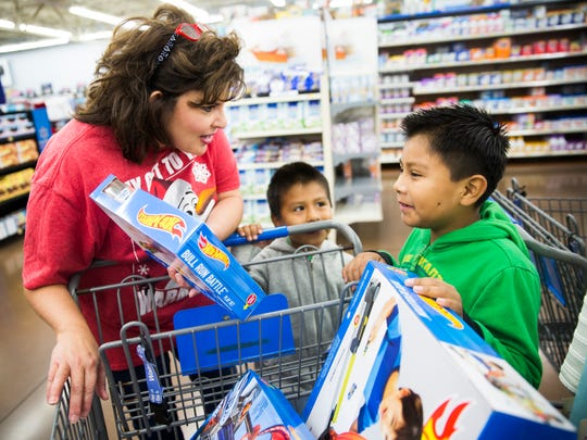 Mary Carney, a volunteer, asks Emanuel Perez, 6, and Giovanni Perez, 7, which toys they're going to play with first during the Joy of Giving event Saturday, Dec. 16, 2017, at a Walmart on Collier Boulevard in East Naples. Hundreds of Collier County families were able to spend $100 for each child, starting at 6 a.m.