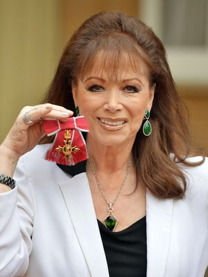 British author Jackie Collins holds her Order of the British Empire (OBE) medal after it was presented to her by Queen Elizabeth II in ceremony at Buckingham Palace on Nov. 28.
