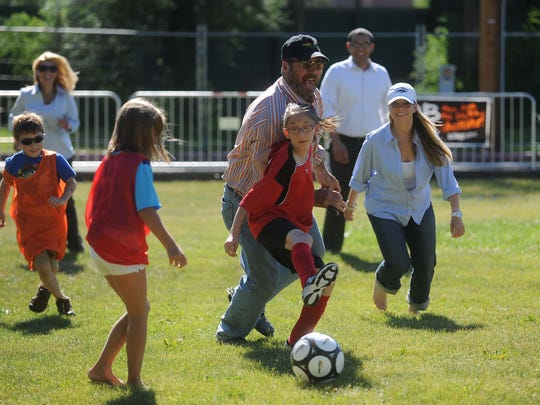 Former Reno City Councilman Dave Aiazzi joins kids playing soccer on the lawn in front of the old Moana Pool.