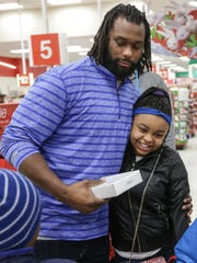 Brandon Pettigrew hugs Ja'Nae Walden, 12, after treating her and five other children to a shopping spree.
