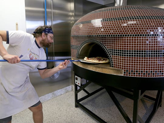 Co-owner James Durawa places a pizza inside the restaurants oven.
