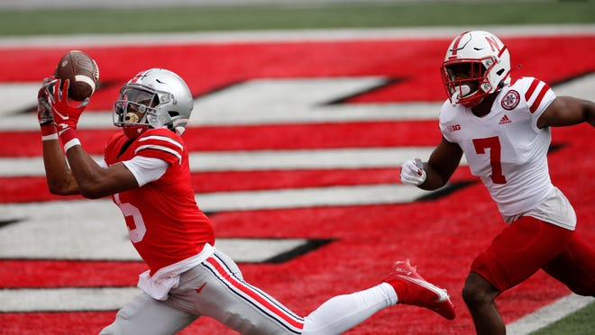 Ohio State receiver Garrett Wilson, left, catches a touchdown pass past Nebraska defensive back Dicaprio Bootle during the first half Saturday in Columbus, Ohio.