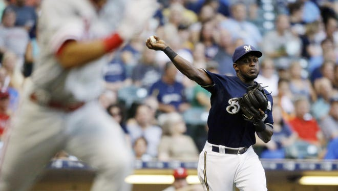 Milwaukee Brewers' Elian Herrera throws out Philadelphia Phillies' Cesar Hernandez, left, during the fifth inning of a baseball game Saturday in Milwaukee.