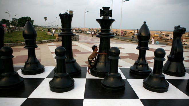 An Indian child plays around a huge chessboard model erected to mark the FIDE World Chess Championship at the Marina beach on the Bay of Bengal coast in Chennai, India.