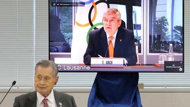 IOC President Thomas Bach, on the screen, communicated with Olympic organizers online on Wednesday. Tokyo Organizing Committee President Yoshiro Mori is at left.