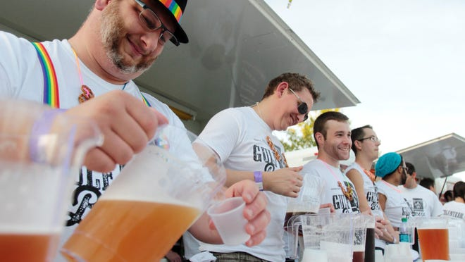 Dale Gauthier, left, and other volunteers serve samples at the Tin Roof Brewing Co. tent in 2014.