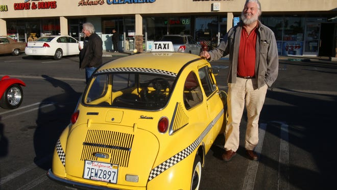 Pat Quilter poses with his 1970 Subaru 360 at a car show  in Huntington Beach, Calif.