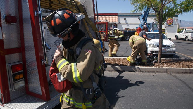 Washington City Fire Department firefighters begin to remove their gear after ensuring that the fire that started in the air conditioning unit on the roof of the Burger King in Washington was completely extinguished Monday, July 27, 2015.