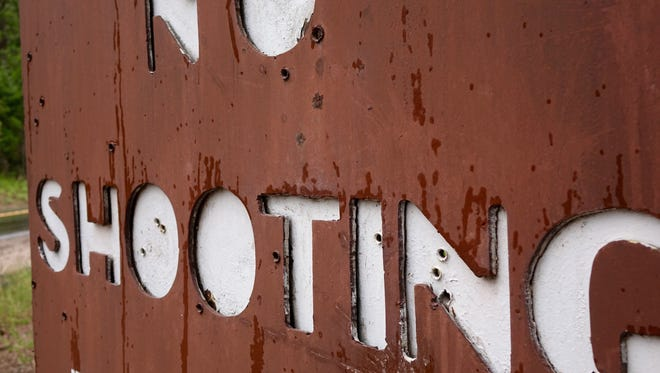 A sign is peppered with bullet holes near Sedalia, Colo., in the Pike National Forest.