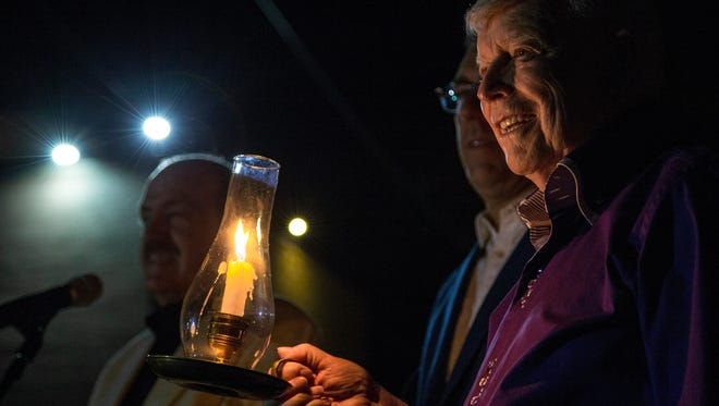 Founder of the Shakespeare Festival, Fred Adams (right), holds a candle at the construction site for Engelstad Shakespeare Theatre, Saturday, Sept. 5, 2015.