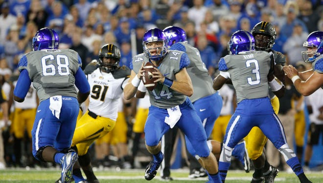 Kentucky Wildcats quarterback Patrick Towles (14) drops back to pass the ball against the Missouri Tigers in the first half at Commonwealth Stadium.