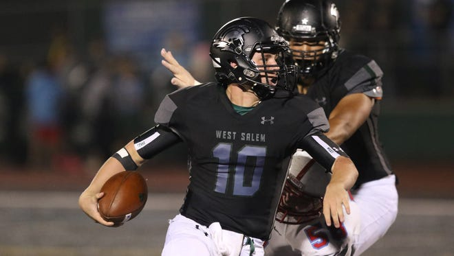 West Salem's Brody Wittman runs the ball as the Titans fall to South Salem in overtime during a game on Friday, Sept. 25, 2015, in Salem.