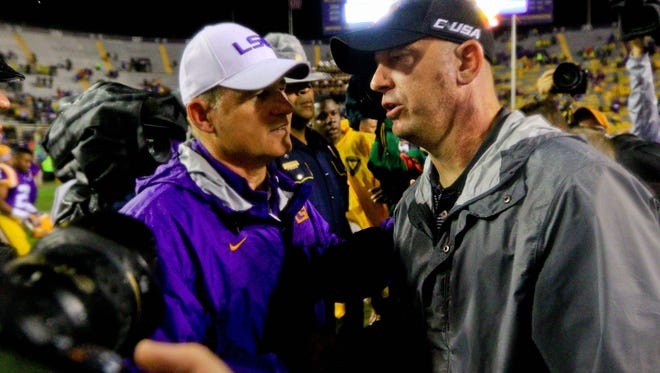 Oct 24, 2015; Baton Rouge, LA, USA; LSU Tigers head coach Les Miles and Western Kentucky Hilltoppers head coach Jeff Brohm meet following a game at Tiger Stadium. LSU defeated Western Kentucky 48-21. Mandatory Credit: Derick E. Hingle-USA TODAY Sports