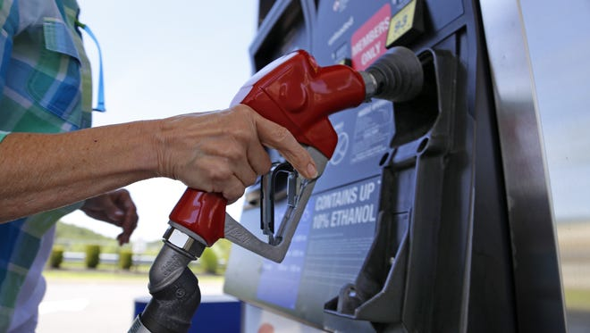 A woman holds a nozzle as she refuels her car.