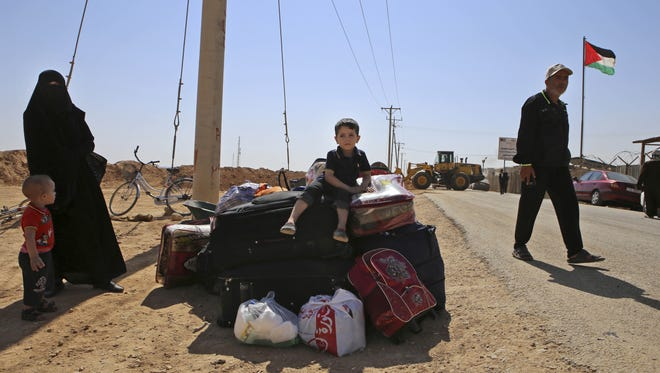In this July 29 photo, a Syrian refugee boy sits on top of his family's belonging while waiting to leave Zaatari refugee camp, in Mafraq, Jordan.