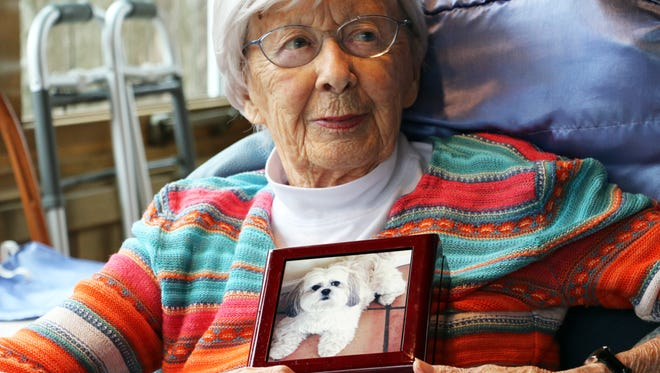 Betty McCoy is pictured with a photo of her late pet dog, Sophie, 16, who was euthanized the day after Thanksgiving. McCoy, 89, who has lived with stage 4 lung cancer for four years, donated $15,000 to the Winneshiek County Sheriff so that the department could replace its police dog that died of brain cancer.