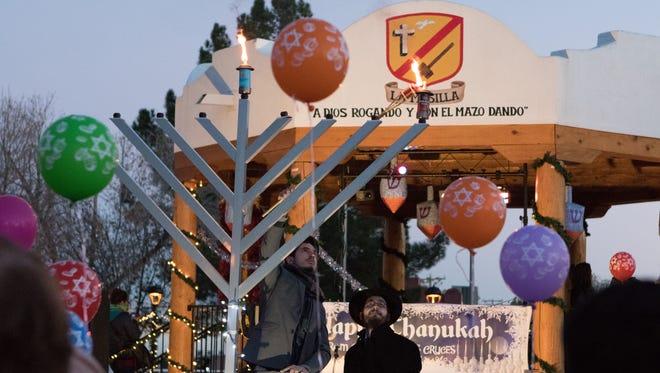 Yosef Peysin lights the Menorah candle while Rabbi Bery Schmukler looks on.