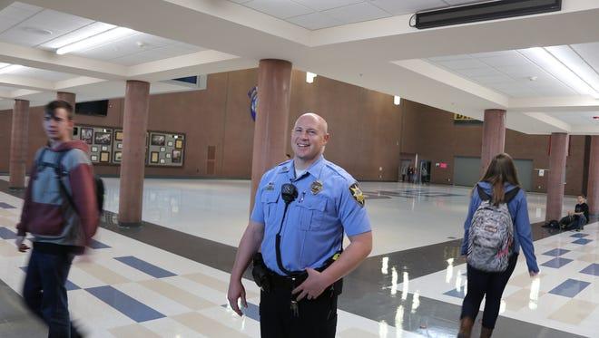 Dixie Middle School Resource Officer Matt Schuman walks the halls as students leave class.