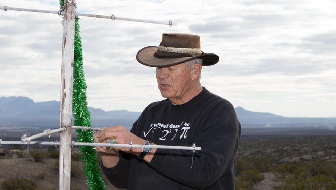 Bob Senecal decorates a tree near his Mesilla Hills home in memory of  close friends and neighbors, Gilles and Helga Delisle, who were savagely shot to death in their nearby home in April 2010.