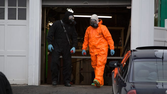 Police in hazmat suits catalog evidence during a meth lab bust at 422 Firth St. in Endicott on Saturday, Jan. 2, 2016.
