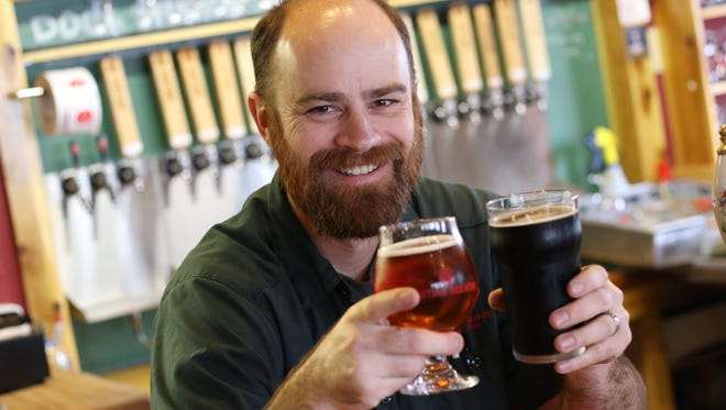 Santiam head brewer and co-owner Jerome Goodrow holds a glass of Diabolus Belgian-style Tripel, left, and Union Pinot Baltic Porter.