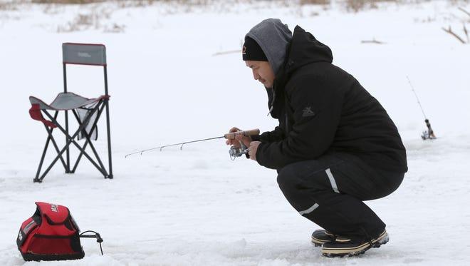 Saul Moua, of Wausau, kneels down while ice fishing on the Wisconsin River near McCleary Bridge in Wausau on January 21, 2016.