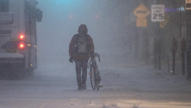 A pedestrian walks his bike down E. Main St. during a snowstorm Friday in Newark.