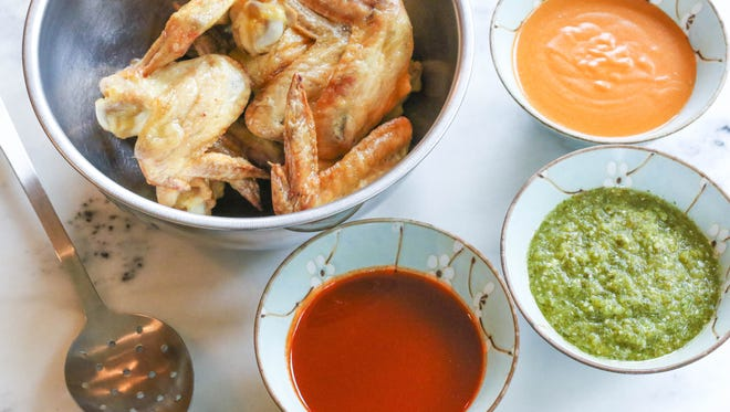 Chicken wings are served with three sauces: Sriracha Agave Garlic, Garlic Pepper Tomatillo and Thai Curry Peanut.