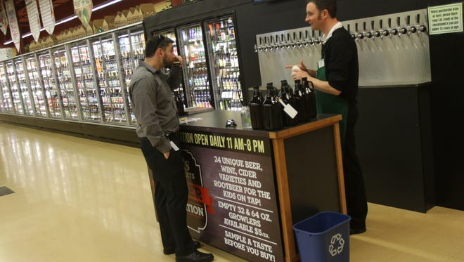 Store manager Jeff Lewis, right, describes a beer being sampled by Daniel Fitterer at the Roth's Sunnyslope Market on Feb. 1, 2016.