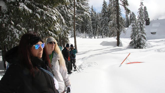 Participants in a ranger-guided snowshoe hike at Crater Lake listen to a briefing by the ranger before the group heads out.