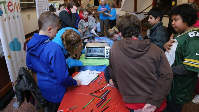Iron County area students work on projects at a STEM Utah booth  at the STEAM Festival and Children's Jubilee at the Heritage Center Theater complex in Cedar City on Friday, Feb. 12, 2016.