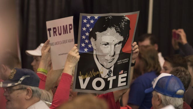 Supporters display signs as  Donald Trump makes a speech in Wichita, Kansas on March 5, 2016.