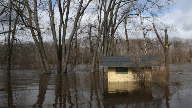 A shed in the backyard of a home along Shore Acres Drive in Biron is cut off from the land due to the rising Wisconsin River after heavy rainfall March 17, 2016.