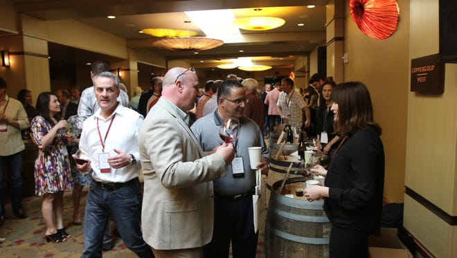 Stoller Family Estate associate winemaker Kate Payne Brown pours wines for two guests at the Willamette: The Pinot Noir Barrel Auction event at The Allison Inn and Spa in Newberg on April 2, 2016.